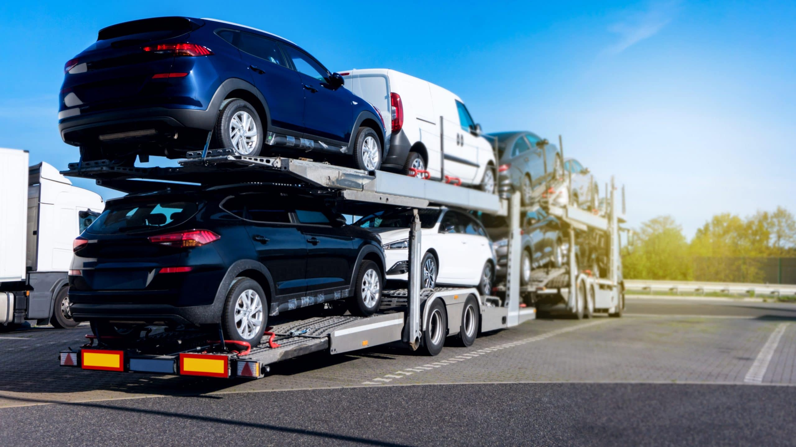 Open trailer auto transportation of new cars